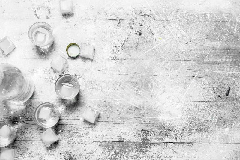 Wodka in einer Flasche und in den Eiswürfeln lizenzfreies stockbild