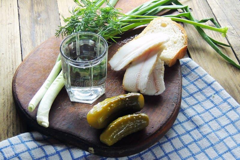 Wodka en komkommer, bacon, knoflook en groene uien stock fotografie