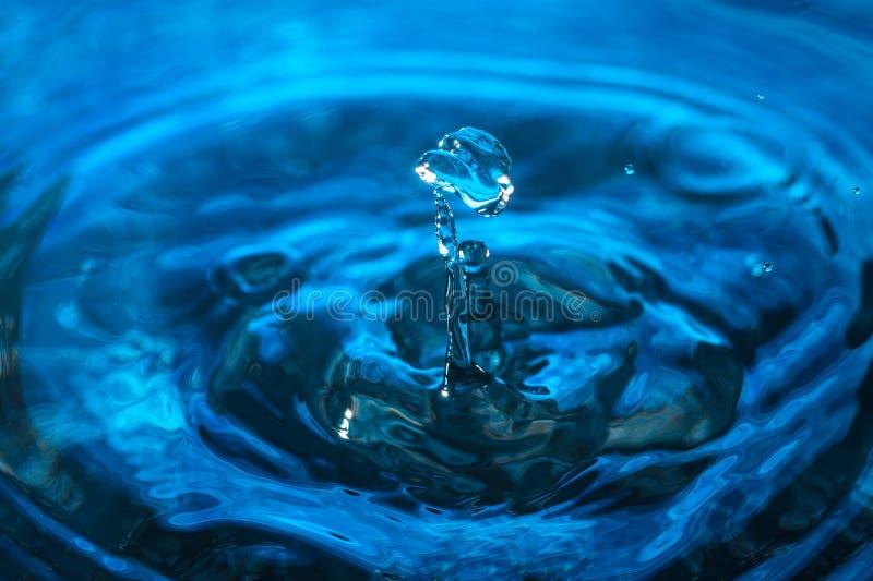 Wodna kropelka na błękitnym tle Zadziwiająca abstrakt woda strzelająca dla tekstury pojęcia odosobniony natury biel fotografia royalty free
