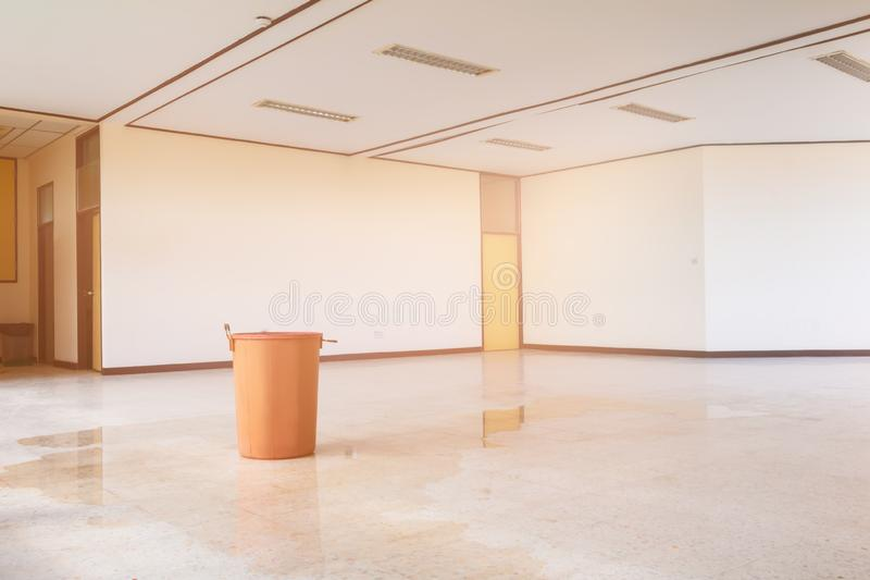 Wodnej przeciek kropli wewnętrzny budynek biurowy w czerwonym wiadrze od sufitu i przepływie na lastryko podłodze obrazy stock