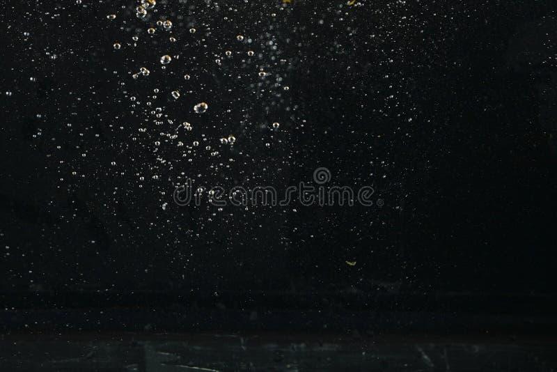 Wodny bąbel w wodzie na czarnych tło fotografia royalty free