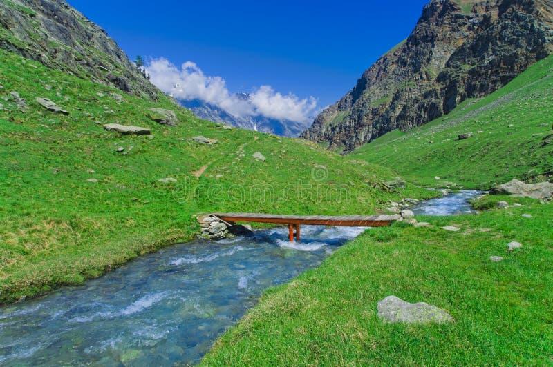Wodny strumień i most w góra krajobrazie, Gran Paradiso zdjęcia royalty free