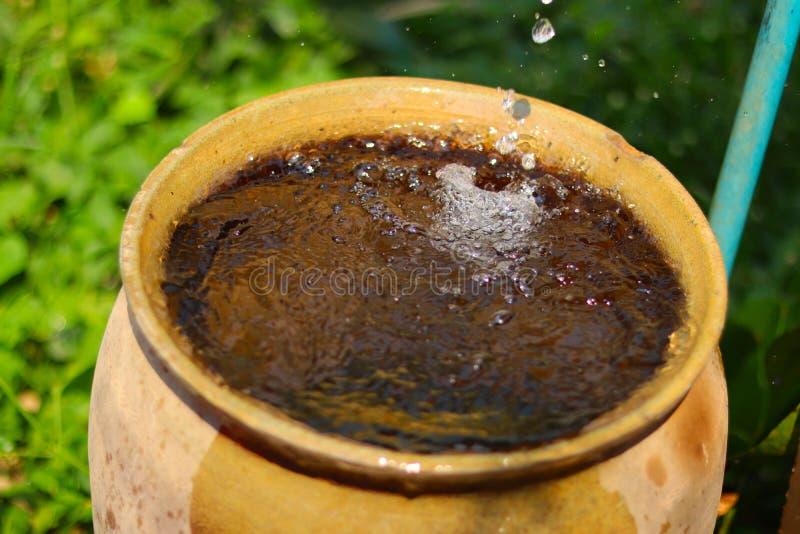 Wodny zrzut od przepuszczać wodnego klepnięcie w rocznika earthenware słój oprócz wodnego pojęcia - obrazy royalty free