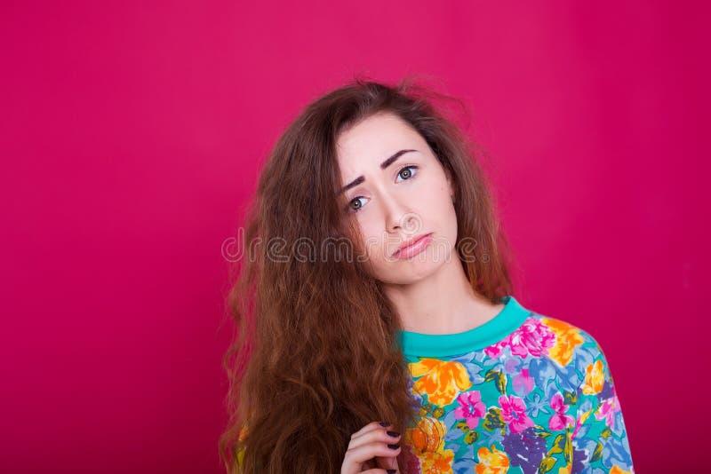 Woede en woedeconcept De jonge expressieve vrouw toont haar slecht gezicht Boos zenuwachtig geërgerd meisjesportret op rode achte royalty-vrije stock afbeelding