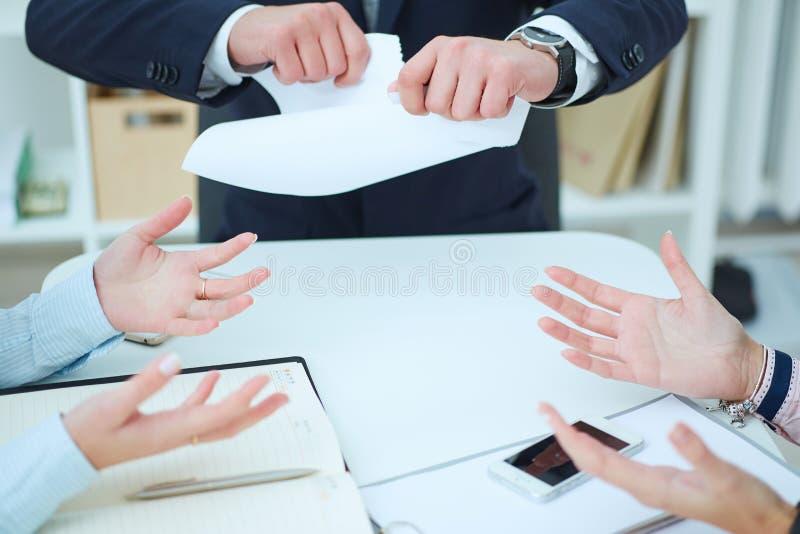 Woedende jonge zakenman tearing omhooggaande arbeidsovereenkomst stock afbeelding