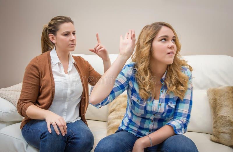 Woedende moeder die met haar tienerdochter debatteren stock foto