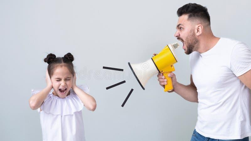 Woedende papa die bij zijn dochter met megafoon gillen stock foto