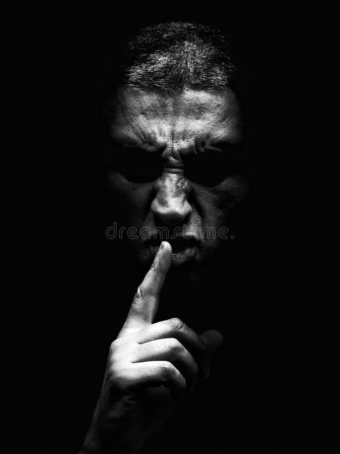 Woedende rijpe mens met een agressieve blik die het stilteteken op een hevige en dreigende manier maken royalty-vrije stock afbeeldingen