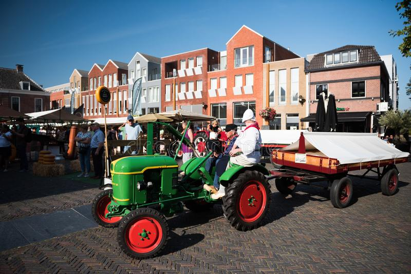 Woerden/Netherlands - August 31 2019: Old tractor at traditional cheese market. Woerden/Netherlands - August 31 2019: Old tractor with farmers at traditional stock photo