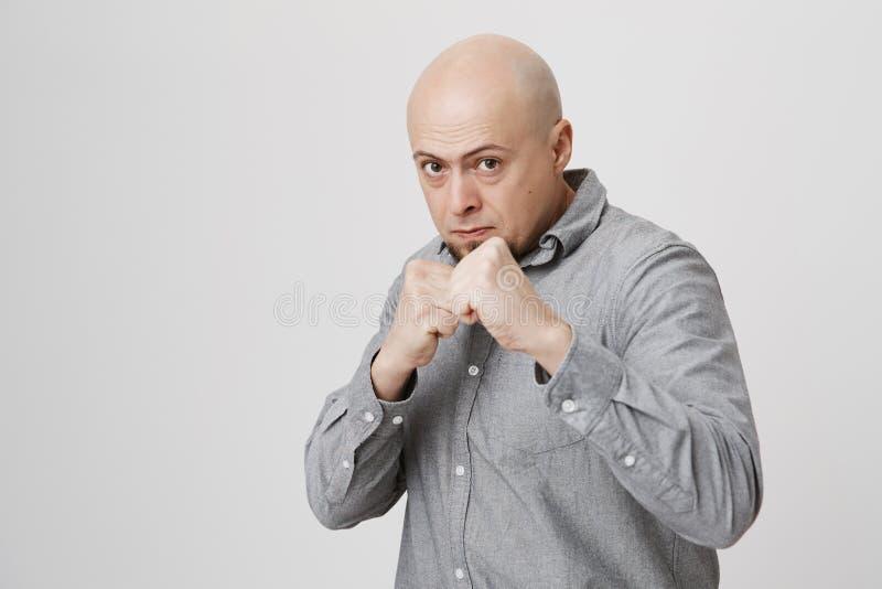 Woest en zeker modieus Europees kaal gebaard mannelijk model in de grijze vuisten van de overhemdsholding voor hem alsof klaar royalty-vrije stock foto