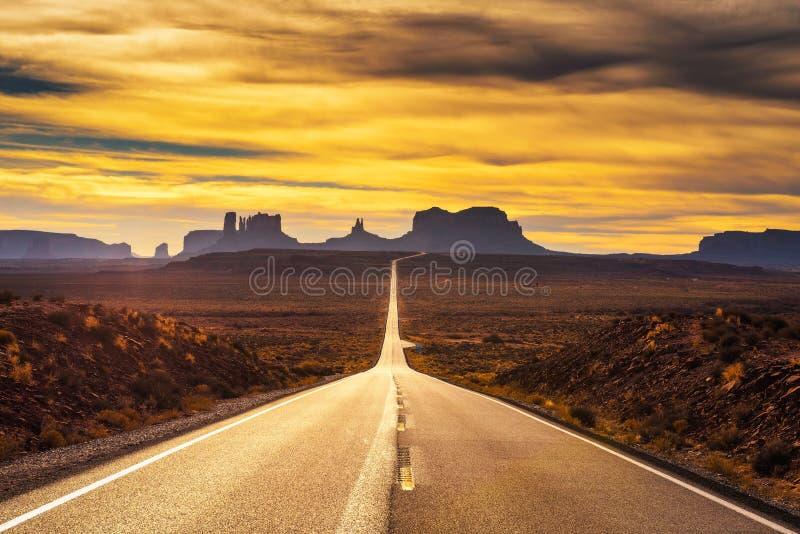 Woestijnweg die tot Monumentenvallei bij zonsondergang leiden stock foto's