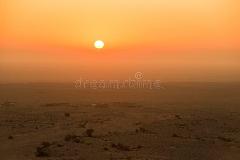 Woestijnzonsopgang en veehoeders` s huizen stock fotografie