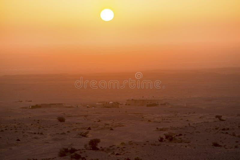 Woestijnzonsopgang en veehoeders` s huizen stock afbeelding