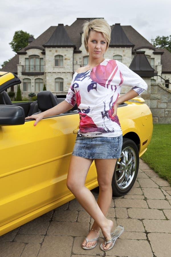 Wohlhabende junge Frau, die neben Auto steht lizenzfreie stockfotos