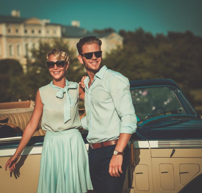 Wohlhabende junge Paare nähern sich klassischem Kabriolett gegen königlichen Palast stockbild