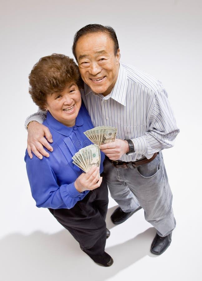 Wohlhabende Paare, die aufgeregt Gruppe twentys anhalten lizenzfreies stockbild