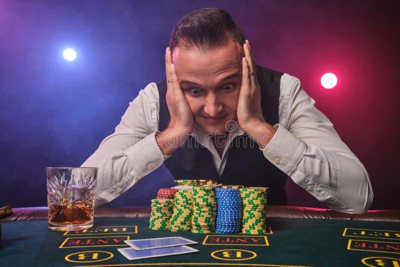 Wohlhabender Mann wirft an einem Schürhakentisch mit Chips und an einem Glas Whisky auf ihm an einem Kasino auf stockbild