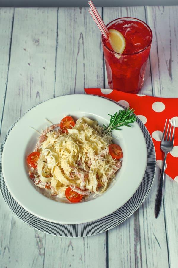 Wohlriechende italienische Paste eines fettuchina mit Speck und Käse mit Fruchtcocktail lizenzfreie stockfotografie