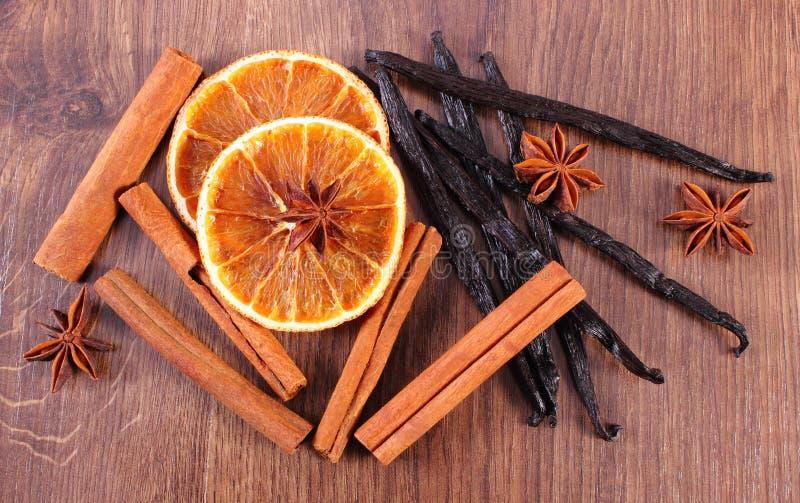 Wohlriechende Vanille, Zimt, Sternanis und getrocknete Orange auf Holzoberfläche stockbild