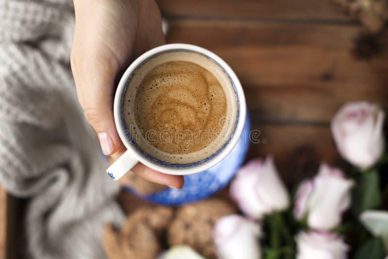 Wohlriechender Kaffee in einer Frau ` s Hand, ein Blumenstrauß von weißen Rosen und Herbstgemütlichkeit Guten Morgen Obere Ansich stockfoto