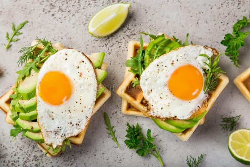 Wohlschmeckende Waffeln mit Avocado, Arugula und Spiegelei zum Frühstück stockfotos