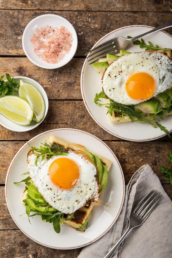 Wohlschmeckende Waffeln mit Avocado, Arugula und Spiegelei zum Frühstück stockbilder