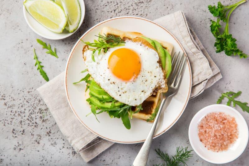 Wohlschmeckende Waffeln mit Avocado, Arugula und Spiegelei zum Frühstück lizenzfreies stockfoto