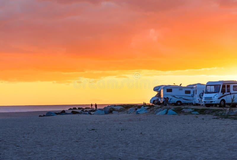 Wohnmobile, Reisemobile am Sonnenuntergangstrand lizenzfreie stockbilder