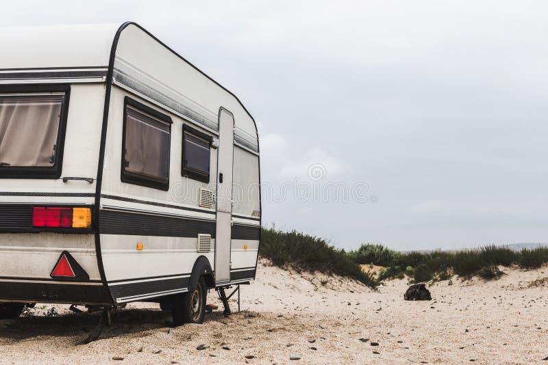 Wohnwagen-Wohnwagenanhänger auf dem Strand Stillstehendes Tourismus-Ferien-Konzept stockfoto