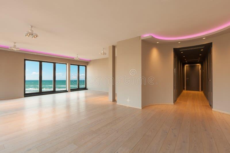 Wohnzimmer in einer modernen Wohnung, Seeansicht lizenzfreie stockfotos