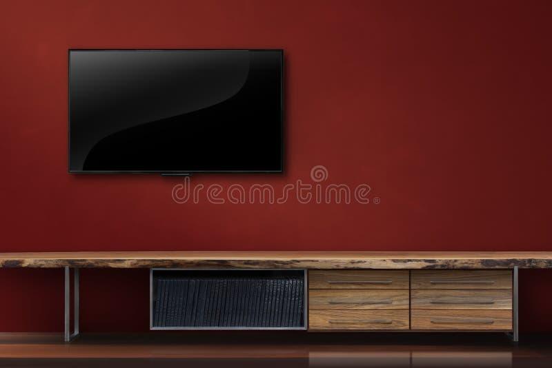 Wohnzimmer führte Fernsehen auf roter Wand mit modernem Dachbodenschweinestall des Holztischs lizenzfreie stockfotografie