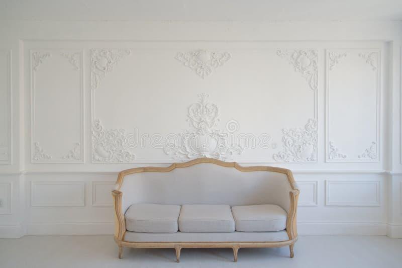 Wohnzimmer mit antikem stilvollem hellem Sofa auf weißen Wandgestaltungsflachreliefstuckformteile roccoco Luxuselementen lizenzfreies stockfoto