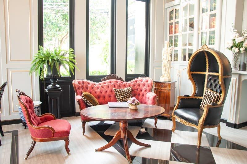 Wohnzimmer mit den roten und schwarzen Stühlen des Modells mit dem Licht von außen lizenzfreie stockfotografie