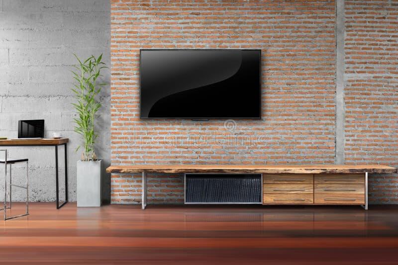 Wohnzimmerfernsehen auf Wand des roten Backsteins mit Holztisch stockfoto