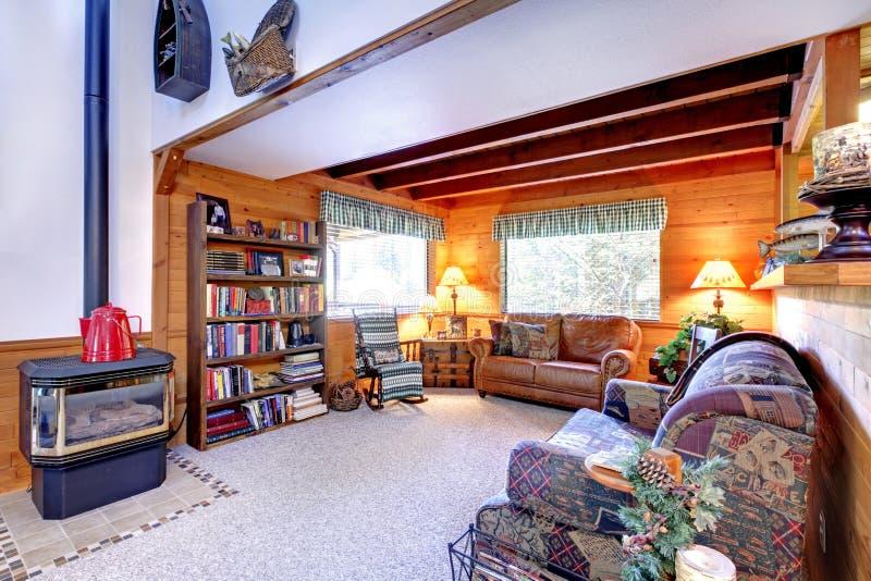 Wohnzimmerinnenraum mit antikem Kamin im Blockhaushaus lizenzfreie stockfotos
