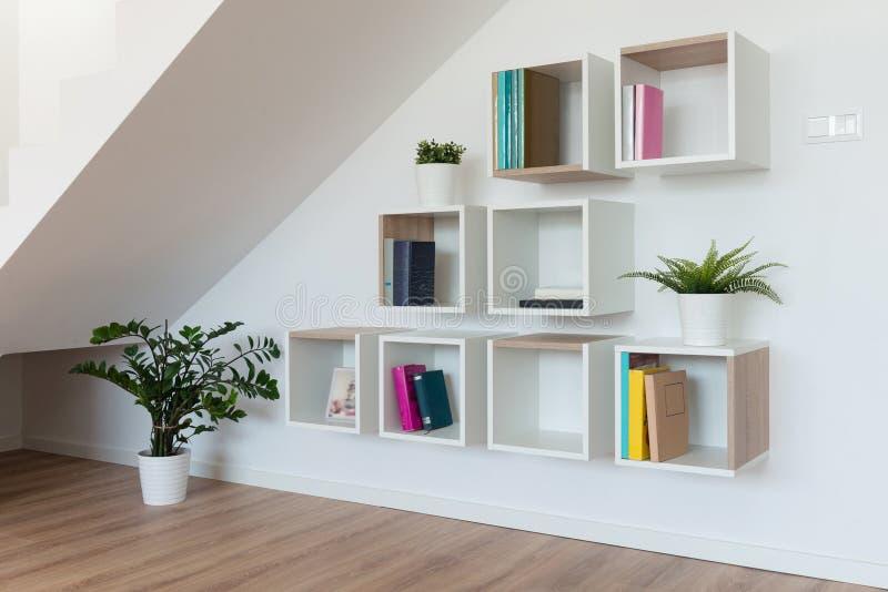 Wohnzimmerinnenraum mit einem Regal für Bücher und Zusätze lizenzfreie stockfotografie