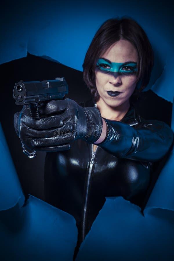 Wojna, brunetka w czarnym lateksowym kostiumu z krócicą nad łamaną papką obraz stock