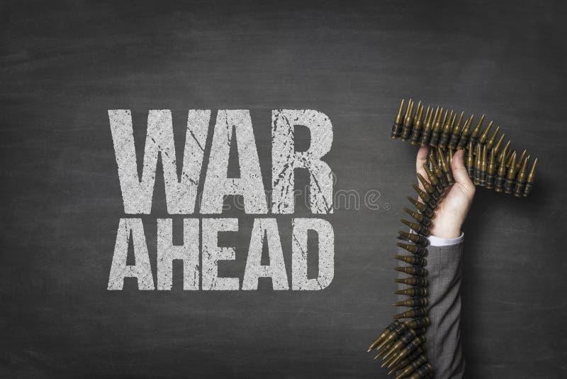 Wojna naprzód tekst na blackboard z biznesmen ręki mienia amunicjami zdjęcie stock