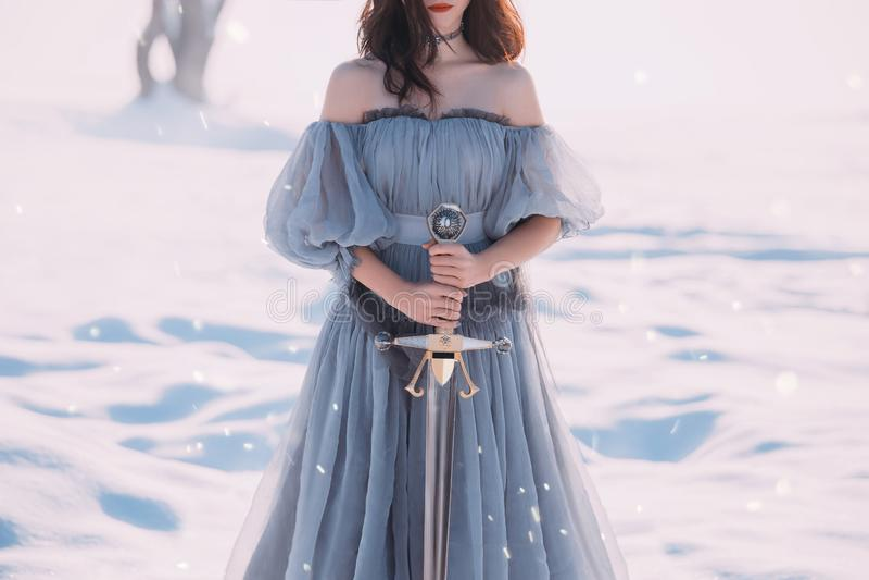 Wojownicza dziewczyna z ciemnym włosy w długiej szarej rocznika światła sukni, damie zimno i mrozie nagich, otwiera ramiona i ost fotografia royalty free