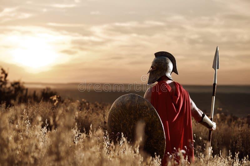 Wojownik jest ubranym żelazną hełma i czerwieni pelerynę fotografia royalty free