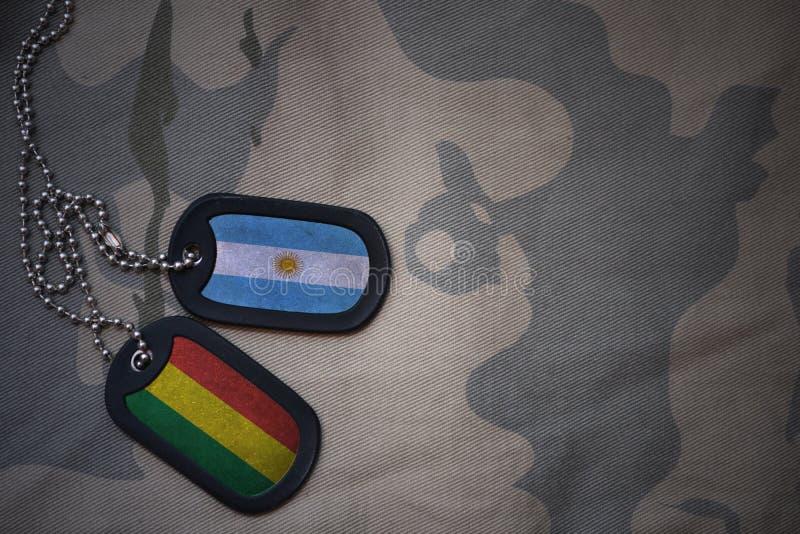 wojska puste miejsce, psia etykietka z flaga Argentina i Bolivia na khakim tekstury tle, ilustracja wektor