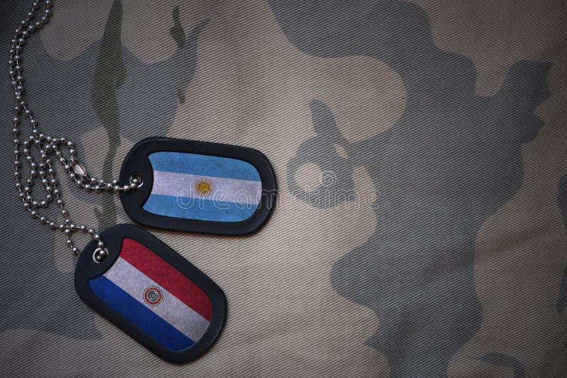 wojska puste miejsce, psia etykietka z flaga Argentina i Paraguay na khakim tekstury tle, royalty ilustracja