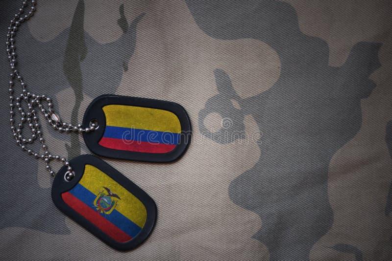 wojska puste miejsce, psia etykietka z flaga Colombia i Ecuador na khakim tekstury tle, zdjęcie royalty free