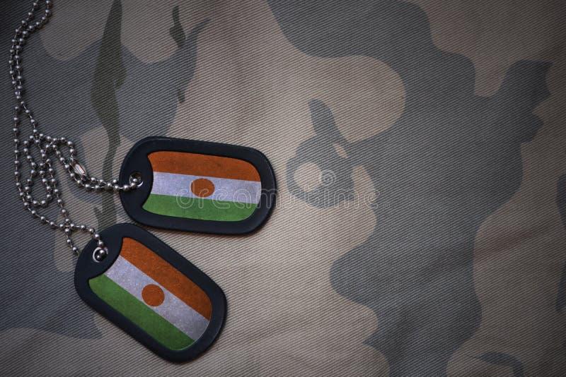 Wojska puste miejsce, psia etykietka z flaga Niger na khakim tekstury tle fotografia stock