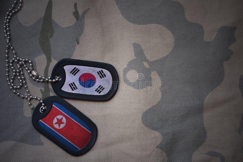 wojska puste miejsce, psia etykietka z flaga południowy Korea i północny Korea na khakim tekstury tle zdjęcie stock