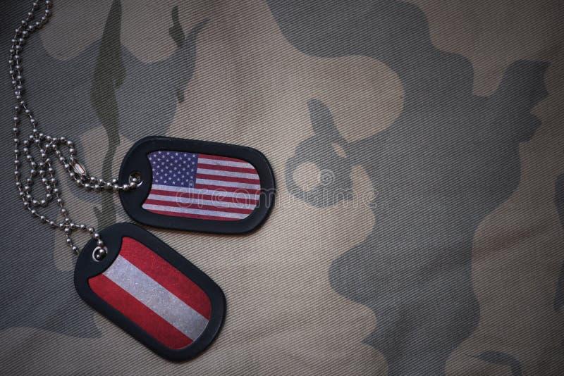 wojska puste miejsce, psia etykietka z flaga zlani stany America i Austria na khakim tekstury tle, fotografia stock