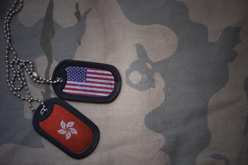 wojska puste miejsce, psia etykietka z flaga zlani stany America i Hong kong na khakim tekstury tle zdjęcia royalty free