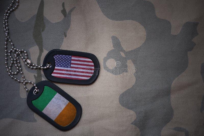 wojska puste miejsce, psia etykietka z flaga zlani stany America i Ireland na khakim tekstury tle, obraz stock