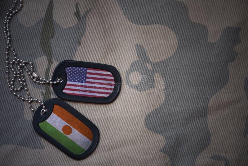 wojska puste miejsce, psia etykietka z flaga zlani stany America i Niger na khakim tekstury tle, zdjęcie stock