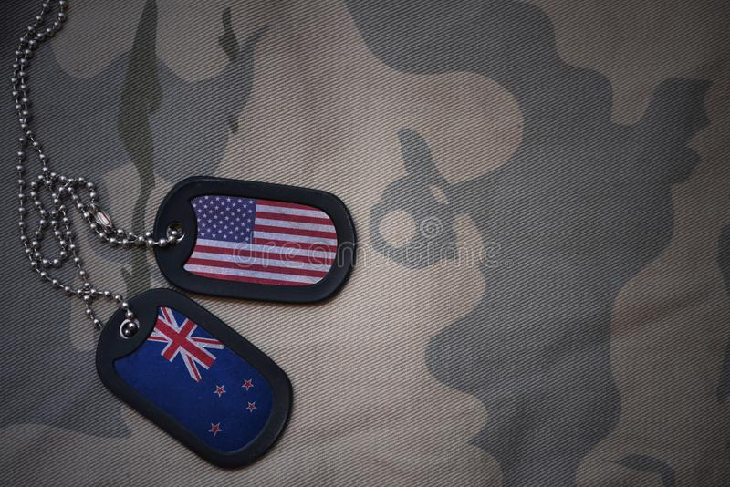 wojska puste miejsce, psia etykietka z flaga zlani stany America i nowy Zealand na khakim tekstury tle, zdjęcie stock